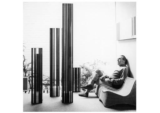 Photo portrait en noir et blanc de Luc Peire, assis dans un fauteil en osier.